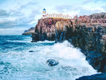 Neist Point lighthouse on rocky cliff above wavy sea. Blue evening sea and sharp cliffs,. Isle of Skye, Scotland Stock Images