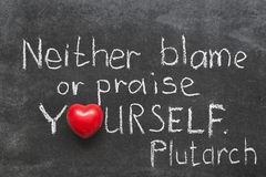Neither blame. Famous Ancient Greek philosopher Plutarch quote about praise or blame yourself handwritten on blackboard Royalty Free Stock Images