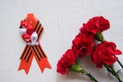 Nejlikablommor och George Ribbon på abstrakt ljus bakgrund dagen för kalender 9 kan den röda segern Jubileum 70 år Royaltyfria Bilder