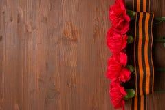 Nejlikablommor och George Ribbon på abstrakt ljus bakgrund dagen för kalender 9 kan den röda segern Jubileum 70 år Arkivbild