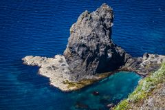 Nekoiwa, Rebun Island, Japan. Nekoiwa, meaning `Cat Rock,` juts out of the blue sea along the green coast of Rebun Island, Japan; view from behind the `cat Royalty Free Stock Photo