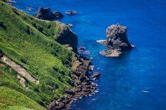 Nekoiwa, Rebun Island, Japan. Nekoiwa, meaning `Cat Rock,` juts out of the blue sea along the green coast of Rebun Island, Japan; a fishing boat floats nearby Stock Images