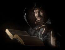 Nekromanten gjuter pass från den tjocka forntida boken, bak genomskinligt exponeringsglas som täckas av vattendroppar på en mörk  Royaltyfri Foto