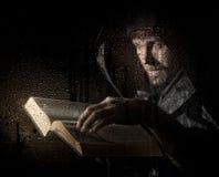 Nekromanten gjuter pass från den tjocka forntida boken, bak genomskinligt exponeringsglas som täckas av vattendroppar på en mörk  Arkivfoton
