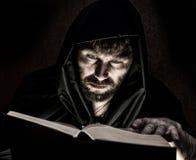 Nekromanten gjuter pass från den tjocka forntida boken vid levande ljus på en mörk bakgrund Arkivbild