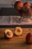 Nektarinenhälften auf hackendem Brett mit Äpfeln im Hintergrund Stockfotos