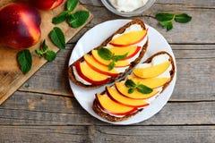 Nektaryna kremowy ser ściska na rocznika drewnianym stole i talerzu Żyto chleba kanapki z świeżymi nektarynami Obrazy Stock
