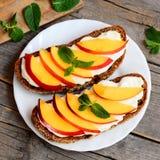 Nektaryna kremowy ser ściska na talerza i rocznika drewna tle Otwarte kanapki Zdjęcia Stock