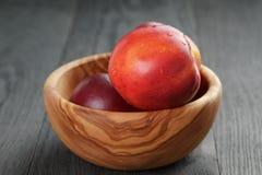 Nektaryny w oliwnym drewnianym pucharze na dębowym stole Obrazy Stock