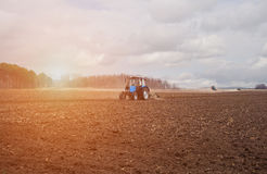 Nel in anticipo, mattina della molla, a causa del legno il sole luminoso sale a Il trattore va e tira un aratro, arante un campo  Fotografie Stock Libere da Diritti