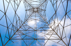 Nel centro del palo di potere ad alta tensione e di chiara parte posteriore del cielo blu Fotografia Stock