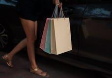 Nel fuoco selettivo dei sacchetti della spesa variopinti stavano tenendo dalla mano di signora, accanto all'automobile fotografie stock