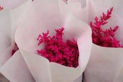 Nel fuoco selettivo di un fiore rosso del fiore in una carta che imballa e che vende al negozio di fiorista fotografia stock