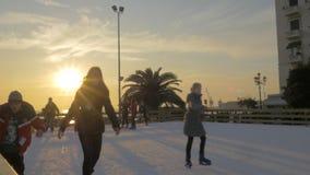Nel giorno soleggiato sulla pista di pattinaggio sul ghiaccio ai bambini pattinanti quadrati di Aristotelous ed ai giovani archivi video