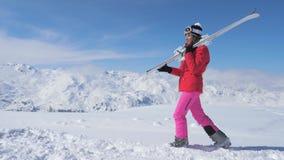 Nel movimento uno sciatore della donna va sulla montagna del pendio, Ski On Her Shoulder video d archivio