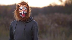 Nel piano medio, un tipo nella maschera della tigre compare a destra Esamina la macchina fotografica e si precipita bruscamente stock footage