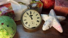 11:55 nel pomeriggio su un vecchio orologio fra i regali di Natale Fotografie Stock Libere da Diritti