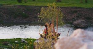 Nel posto di stupore alla natura accanto di giovani signore attraenti di un grande lago praticare la meditazione di yoga li ha co stock footage