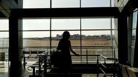 Nel rifugio dell'aeroporto la bella femmina sta camminando lentamente su e giù stock footage