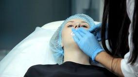 Nel salone di bellezza il medico-cosmetologo prepara la ragazza alla procedura per l'aumento del labbro stock footage