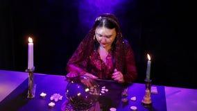 Nel salone magico, lo zingaro legge il futuro sulle pietre bianche in un soffio di fumo archivi video