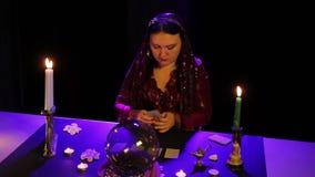 Nel salone magico, lo zingaro presenta le carte sulla tavola nera nell'abbagliamento video d archivio