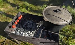 Nel vecchio calderone sul barbecue che cucina porridge contro uno schiarimento della foresta a mezzogiorno Fotografia Stock