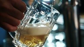 Nella barra, il primo piano, una birra leggera è versato nella tazza stock footage
