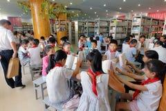 Nella biblioteca di scuola, gli studenti studiano seriamente Immagini Stock