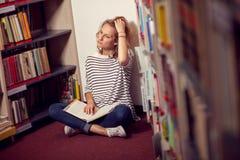 Nella biblioteca, nella ragazza o nella giovane donna dello studente con i libri Fotografie Stock