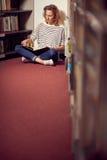 Nella biblioteca, nella ragazza o nella giovane donna dello studente con i libri Fotografie Stock Libere da Diritti