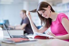 Nella biblioteca - studentessa graziosa con il computer portatile ed i libri Fotografie Stock Libere da Diritti