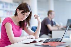 Nella biblioteca - studentessa graziosa con il computer portatile ed i libri Immagine Stock