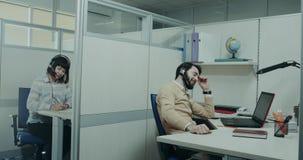 Nella call center, il lavoratore carismatico che parla con il cliente che per mezzo della cuffia felice e sorridendo fa le note E video d archivio