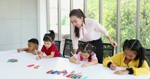 Nella classe di arte, gli studenti asiatici disegnano coscientemente stock footage