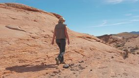Nella donna di sport del movimento che fa un'escursione sul canyon rosso della roccia in deserto video d archivio