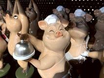 Nella finestra del negozio nei maiali variopinti dei giocattoli del deposito in cappelli del cuoco unico fotografia stock libera da diritti