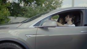 Nella guida delle coppie di amore nell'automobile moderna grigia e nella conversazione stock footage