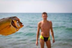 Nella priorità alta un pesce affumicato nei precedenti è un tipo che sta nell'acqua di mare Immagine Stock Libera da Diritti