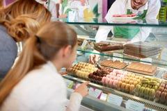 Nella ragazza di negozio della pasticceria scelga i macarons dalla vetrina Fotografia Stock Libera da Diritti