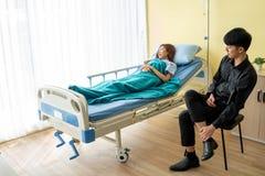 Nella stanza paziente, il paziente della giovane donna dorme dovuto affaticare dalla malattia Con un ragazzo che si siede per inc fotografia stock