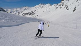 Nella vista della parte posteriore del movimento, sciatore della donna che scia in discesa della località di soggiorno di montagn stock footage