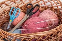 Nelle bobine di una disposizione del canestro di filato, dei ferri da maglia e dello scissors_ fotografie stock libere da diritti