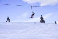 Nelle montagne, nelle alpi, gli sciatori scalano sulle seggiovie per andare ai pendii dello sci fotografia stock libera da diritti