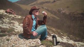 Nelle montagne si siede un uomo in un cappello da cowboy, in un bomber, nelle blue jeans e nei vetri Un t? bevente dell'uomo da u stock footage