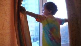 Nelle prime ore del mattino il bambino apre le tende, i raggi del sole attraversa la finestra ALBA video d archivio
