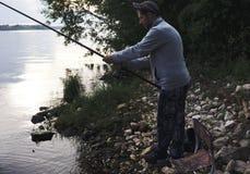 Nello scuro il pescatore con una canna da pesca a disposizione Immagine Stock