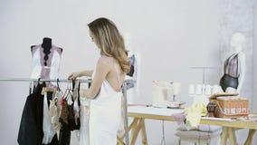 Nello studio, una giovane donna cammina su al gancio e prende una cosa stock footage