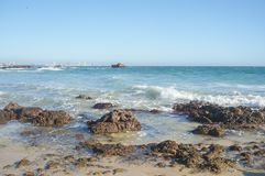 Nelson Mandela Bay-Strand mit den Felsen, die in Richtung Hafen cran blicken lizenzfreie stockbilder