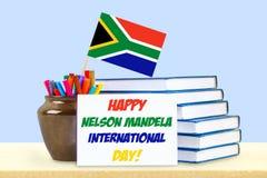 Nelson Mandela-Grußkarte Bücher, Bleistifte Flagge und Postkarte auf einem blauen Pastellhintergrund 18. Juli Stockfotografie
